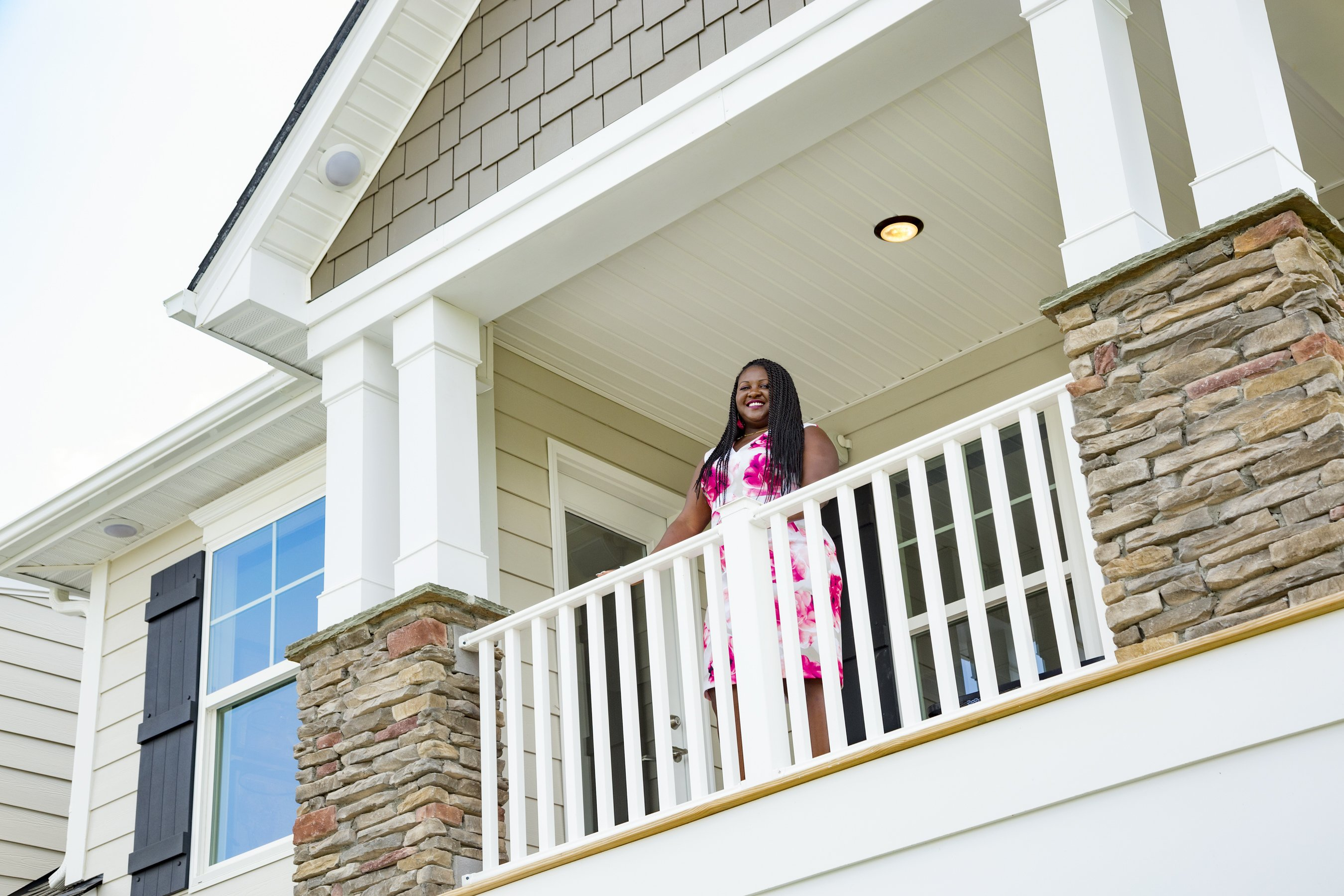 Young Woman standing on balcony of new home